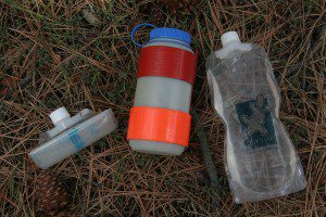 This combination of water bottles works well. The rigid Nalgene in the middle is used for drinking and the Paltypus soft bottle are used to store extra water in the pack.